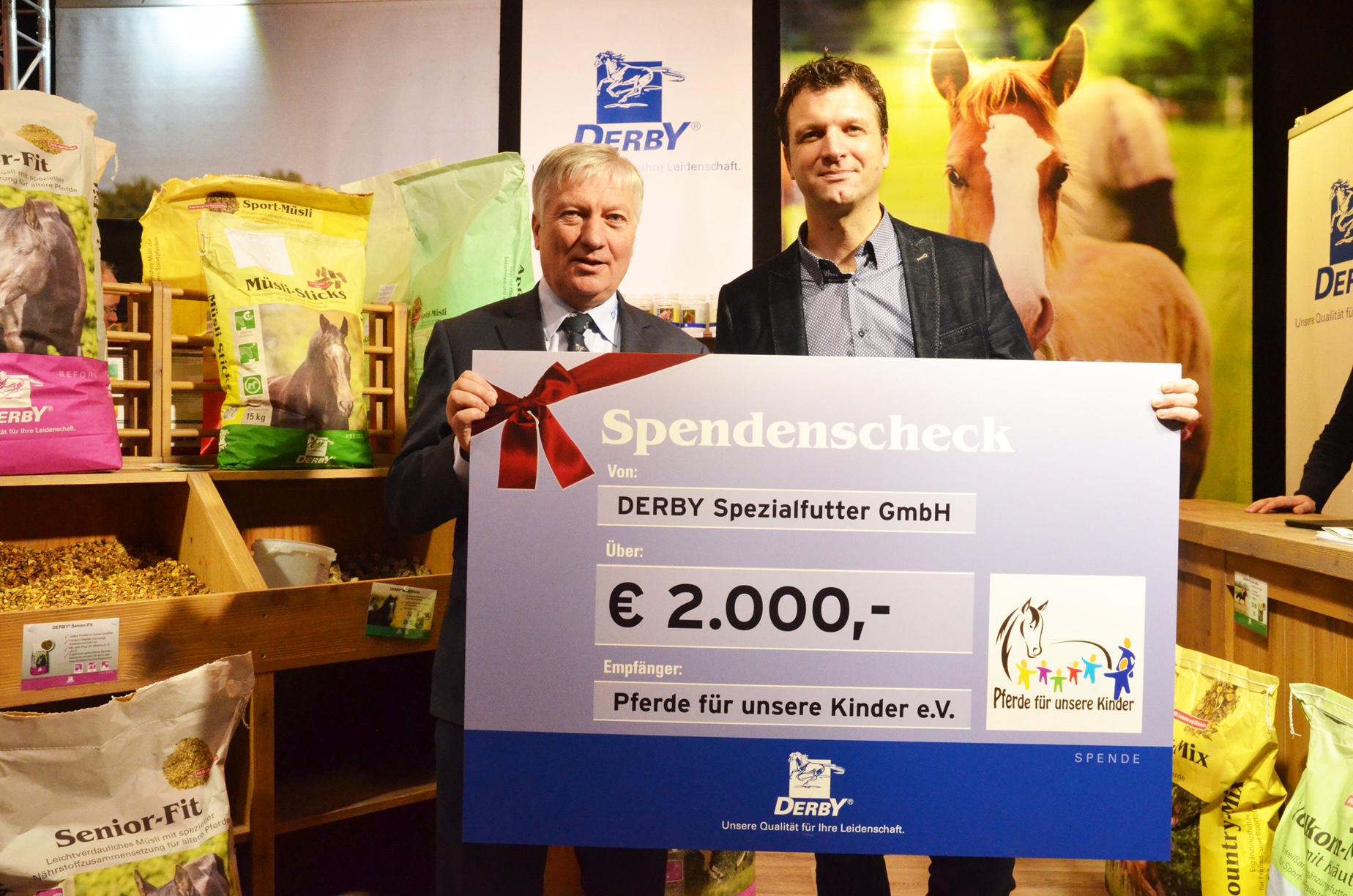 """Dr. Hans-Peter Karp, Geschäftsführer der Derby Spezialfutter GmbH (li.), übergibt den Spendenscheck an Georg Ettwig vom Verein """"Pferde für unsere Kinder e.V.""""."""