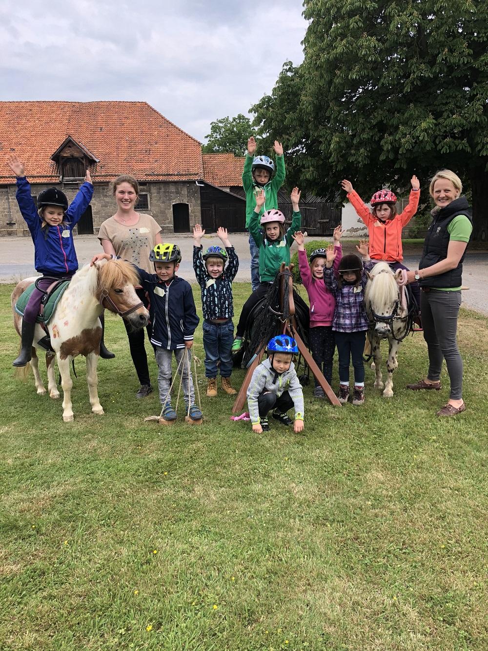 Gruppenbild: Kinder, Ponys, Holzpferd