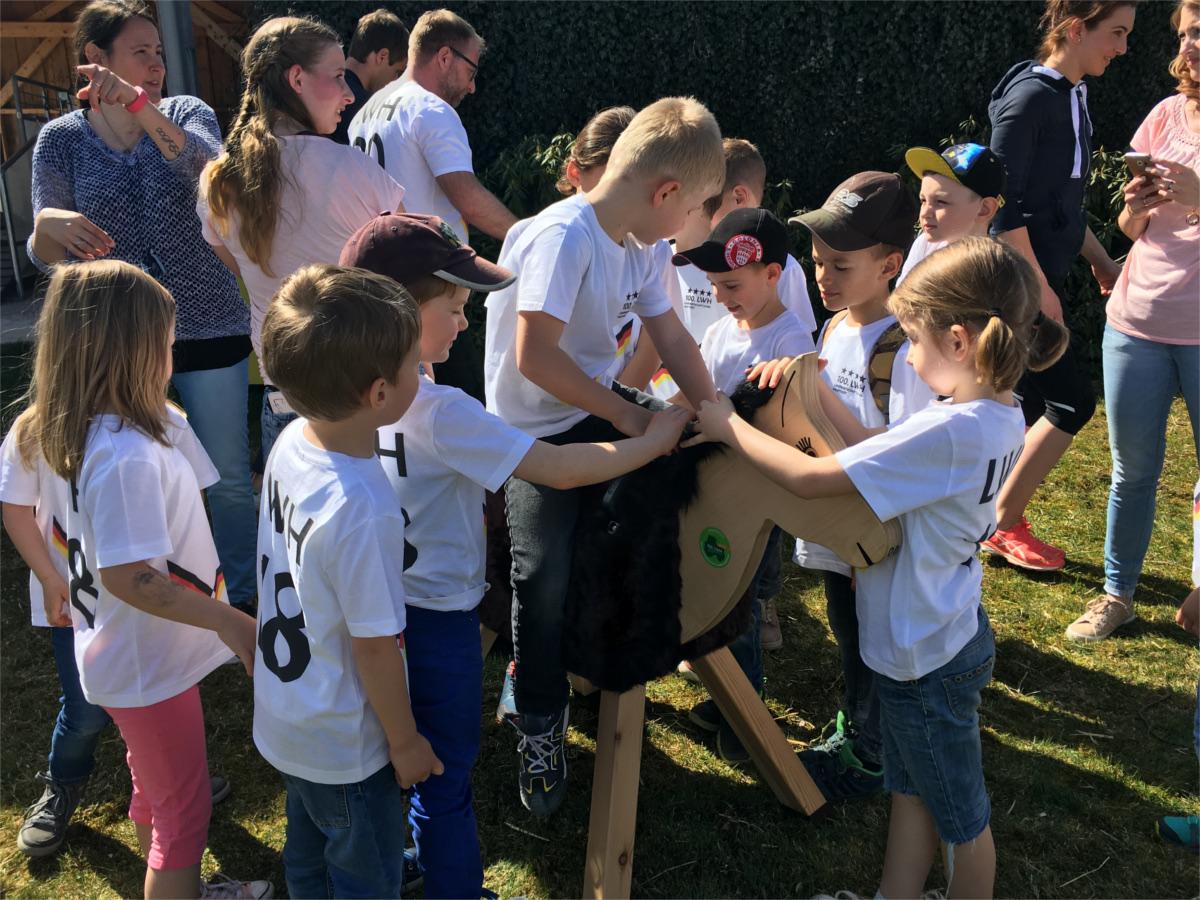 Kinder und Holzpferd auf dem Gestüt von Lisa und Thomas Müller