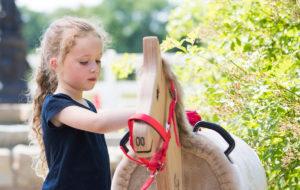 Kind striegelt Holzpferd - Pferde für unsere Kinder e.V. - c Thomas Hellmann (1200x670)